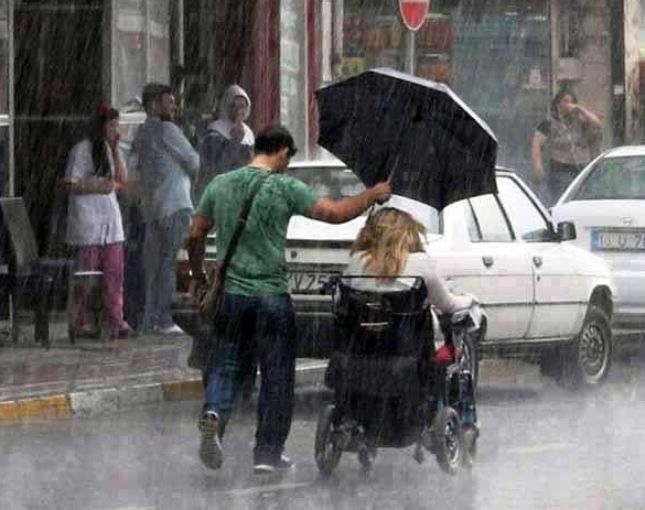Kindness-Man-holding-umbrella-in-rain-woman-in-wheelchair